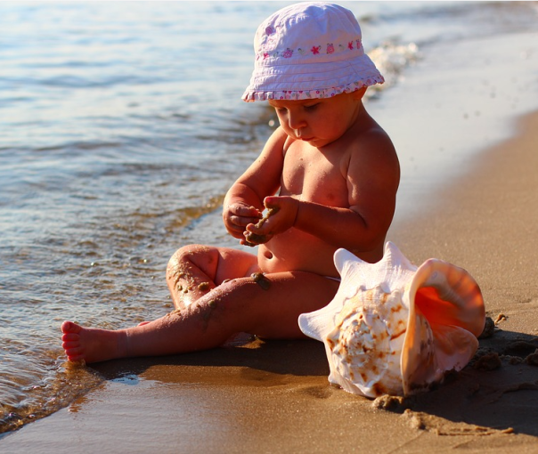 baby at beach big seashell